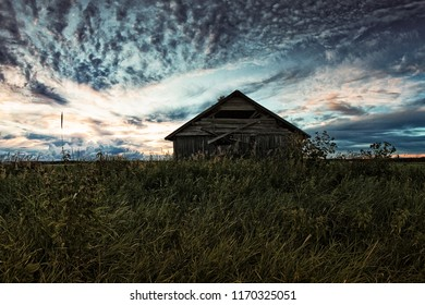The summer sun sets dramatically behind the old barn house in the rural Finland. The autumn is coming and the summer is almost over.