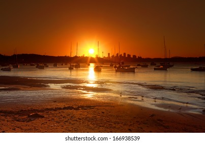 The summer sun setting over Watsons Bay, near Vaucluse, Sydney, Australia. Silhouette of moored yachts and Sydney city in distance