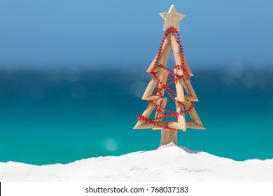 Summer sun shines down on a driftwood Christmas tree decorated with a string of red baubles on a beautiful white sandy beach with ocean background blur and copy space