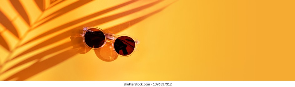 summer sunlight with palm leaf shadow with summer sunglasses on yellow background in sunlight in holiday vacation.banner copy space for display of design.