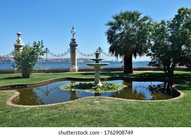 Summer sunny day in the park of Istanbul. On the lawn, in the pool with water lilies there is an elegant fountain. Through the openwork fence you can see the Bosphorus and many city buildings.