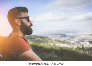 Summer sunny day. Side view of a young bearded man in sunglasses and a brown T-shirt standing on the highest point, looking at the landscape from a bird's flight. Tourist enjoying the view.