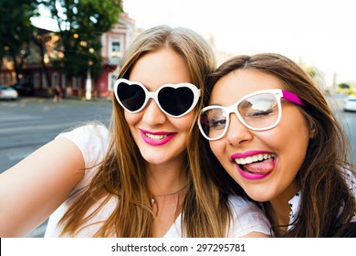Summer sunny image of two sisters best friends brunette and blonde girls having fun on the street, making selfie,wearing funny vintage sunglasses, bright stylish make up long hairs.