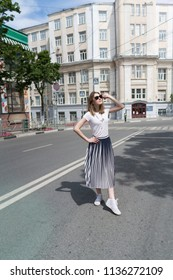 Summer sunny lifestyle fashion portrait of young stylish hipster woman walking on the street, wearing cute trendy outfit,