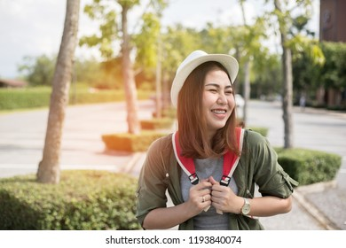 Summer sunny lifestyle fashion portrait of young stylish hipster Asia woman walking on the street