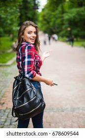 Summer sunny lifestyle fashion portrait of young stylish hipster woman walking on street