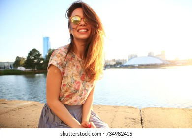 Summer sunny lifestyle fashion portrait of young stylish hipster woman. Woman with white teeth thinking and looking sideways in a park in summer