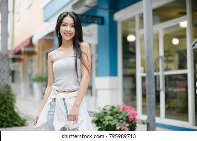 Summer sunny lifestyle fashion portrait of young stylish hipster woman walking on the street, wearing cute trendy outfit