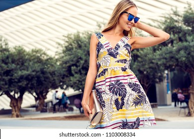 Summer sunny lifestyle portrait of young stylish blonde woman in the park,wearing cute trendy dress,drinking coffee. Fashion photo