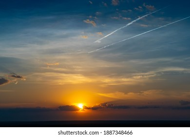 Summer sunrise with clouds and vapour trail in the sky
