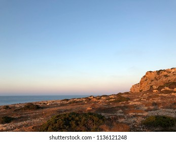 The summer sunrise of coast of the Mediterranean Sea on the abrupt rock of the island of Cyprus
