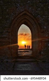 summer sunrise on glastonbury hill, through glaatonbury tor arch