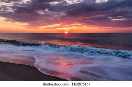 A summer sunrise over the Atlantic Ocean lights up both the sky and surf alone the beach.