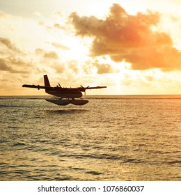 Summer sunrise with seaplane. Landing seaplane on the seashore. Calm scenery on morning sea.