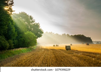 Summer sunrise view on harvested field with straw bales in the Bohemina Paradise, Czech Paradise