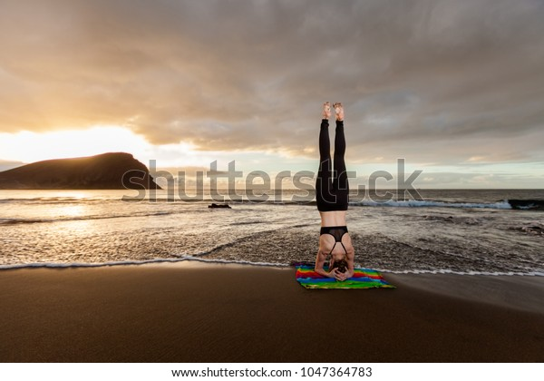 Summer sunrise yoga session on beautiful Playa de La Tejita beach with view on atlantic ocean and Punta Roja rock - tropical Tenerife island, Canary in Spain. Supported Headstand, Salamba Sirsasana