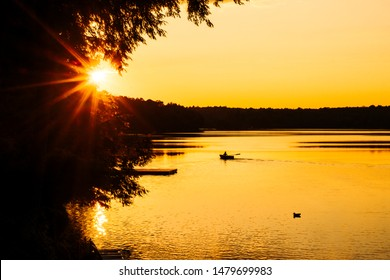 SUMMER SUNSET WITH BOAT ON LAKE - Beautiful yellow sunset on water with canoe/boater paddling in distance. Serene, peaceful scene, with silhouetted person and Canadian loon/duck/bird. Ontario, Canada
