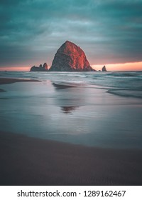 Summer sunset at Haystack Rock, an iconic monolithic rock at Cannon Beach in Clatsop County, Oregon, USA.