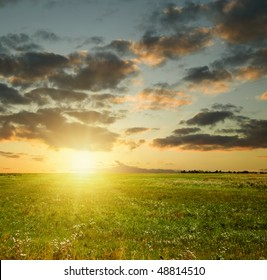 Summer sunset landscape. Field and sky with dark clouds