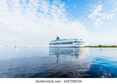Summer sunset. Large white passenger ship and a pilot boat in the Baltic Sea, close-up. Latvia