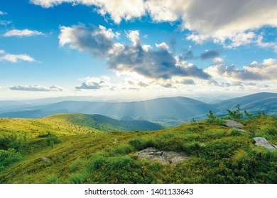 summer sunset in mountains. rocks among the grass on rolling hills. sun behind the cloud above the distant ridge. dynamic cloudscape and refreshing breeze. beautiful nature background