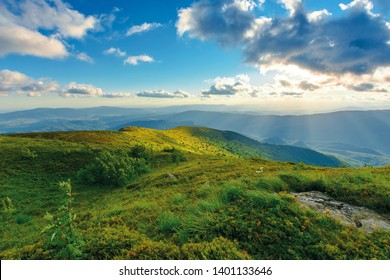 summer sunset in mountains. rocks among the grass on rolling hills. sun behind the cloud above the distant ridge. dynamic cloudscape and refreshing breeze. beautiful nature scenery