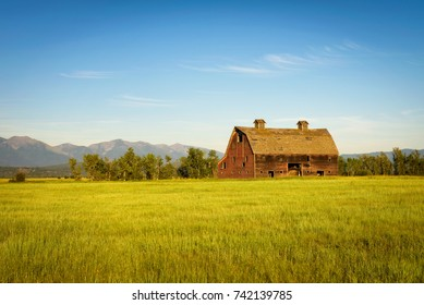 Summer sunset with an old barn in rural Montana with Rocky Mountains in the background.