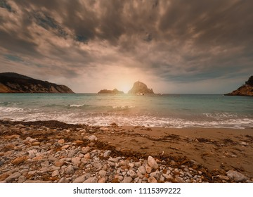 Summer sunset on the beach of Cala D'hort, Ibiza, Spain. In the background the islets of Es Vedrá and Es vedranell