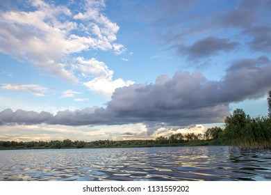 Summer sunset over a lake with evening clouds