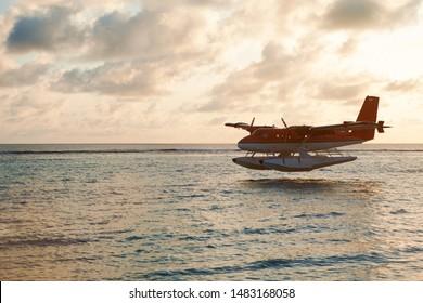 Summer sunset with seaplane. Landing seaplane on the dawn seashore. Calm scenery on evening sea.