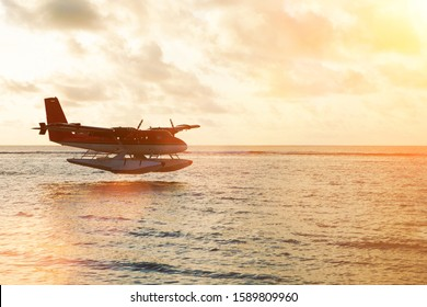 Summer sunset with seaplane. Landing seaplane on the dawn seashore. Calm scenery on evening sea.