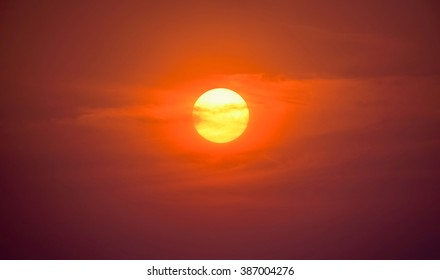 Summer sunset. The setting sun in a cloudy sky background.