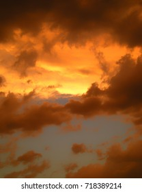 Summer sunset sky with dark and glowing orange clouds.
