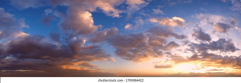 Sommersonnenuntergang Himmelspanorama mit floralen Wolken. Sommerabend bei gutem Wetter Himmelshintergrund.