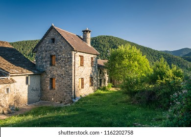 Summer sunset in the village Nerin in spanish Pyrenees. Old, stone house is surrounded with green: grass, trees and forests in the background. Peaceful, and quiet mood in this evening scene.