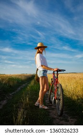 Summer sunset and woman on bike
