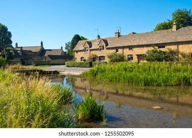 Summer sunshine on the well known visitor attraction of picturesque Lower Slaughter village in the Cotswolds AONB (Area Of Outstanding Natural Beauty) in Gloucestershire, UK
