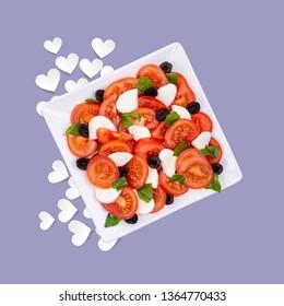 Summer Sunshine salad of Tomato, Basil, Black  Olives and Mozzarella on a coloured background with white hearts