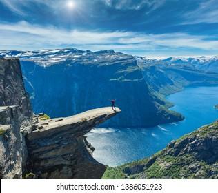 Die Sommersonne von Trolltunga (berühmtes nordvegisches Ziel der Trollzunge) und Ringedalsvatnet See in Odda, Roldal, Norwegen. Ein Mensch, der auf Felsen touristisch ist.