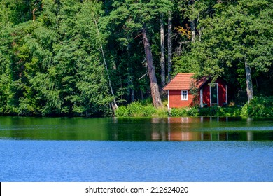 Summer in Sweden - traditional red little cabin at a lake