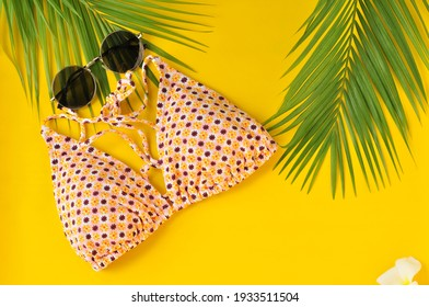 Summer swimwear theme with sunglasses and flowers on a yellow background.