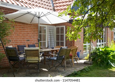 summer terrace at the house with table and many chairs under a sunshade for a meal with the whole family
