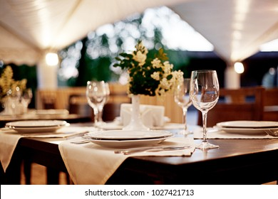 Summer terrace of the restaurant. On the tables, serving with white plates of wine glasses and white vases with the colors of the bride
