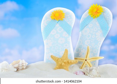 Summer theme of cutout flip flops stuck in beach sand with shells and starfish scattered around. A blue sky with puffy white clouds is in the background. Copy space.