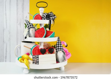 Summer theme on-trend farmhouse aesthetic three tiered tray decor filled with summer fruit, black plaid gnomes, and farmhouse style stack of books mockups. Modern yellow background. Copy space. - Shutterstock ID 1967873572