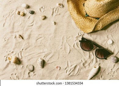 Summer theme. Shells, sea stones, sunglasses and straw hat on white sand as background. Flat lay