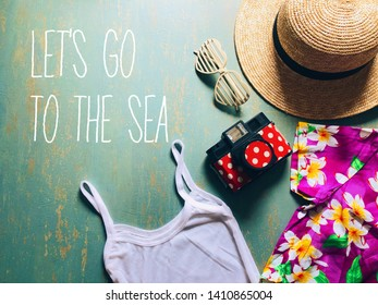 Summer theme straw boater hat with black ribbon, plastic heart shaped glasses, toy camera, white camisole, colorful hawaiian shirt on vintage green background with typography LET'S GO TO THE SEA.