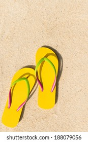 Summer theme with yellow flip flop on sandy beach