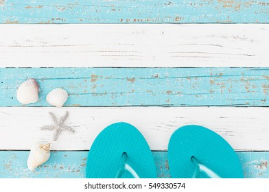 Summer time background, blue beach shoes, sea shells and starfish objects on turquoise white wood.