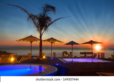 Summer time: beautiful dawn at pool area with palm and parasols, Tropea, Italy